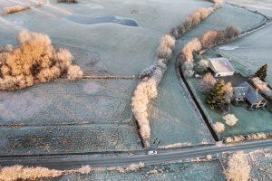 Drohnenfotografie in Schleswig-Holstein über einem Feld und Seenlandschaft bei Schnee