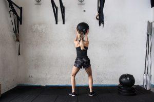 Blonde sportliche Frau in der Crossfitbox mit Crossfitball in den Händen