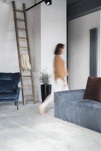 Interiorfotografie Hamburg im Scandi Look mit dunkelblauem Samt Sessel und grauem Beton mit Person in Bewegungsunschärfe