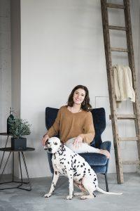 Interiorfotografie Hamburg im Scandi Look mit dunkelblauem Samt Sessel und grauem Beton mit Person