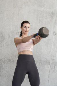 Sport und Fitnessfotografie Lifestyle Portrait in Hamburg in der Hafen City Frau macht Fitnessübungen mit Kettleball