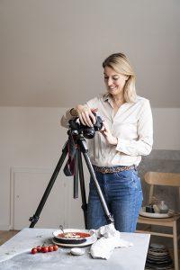 People Portraitfotografie und Lifestyle Fotografie in Kiel und Hamburg Blonde Frau in Cremetönen hält Stapel an Schüsseln in der Hand und blickt in die Kamera